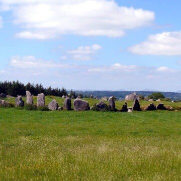 Standing stones in a wide circle in a green Irish field under blue skies with fluffy clouds