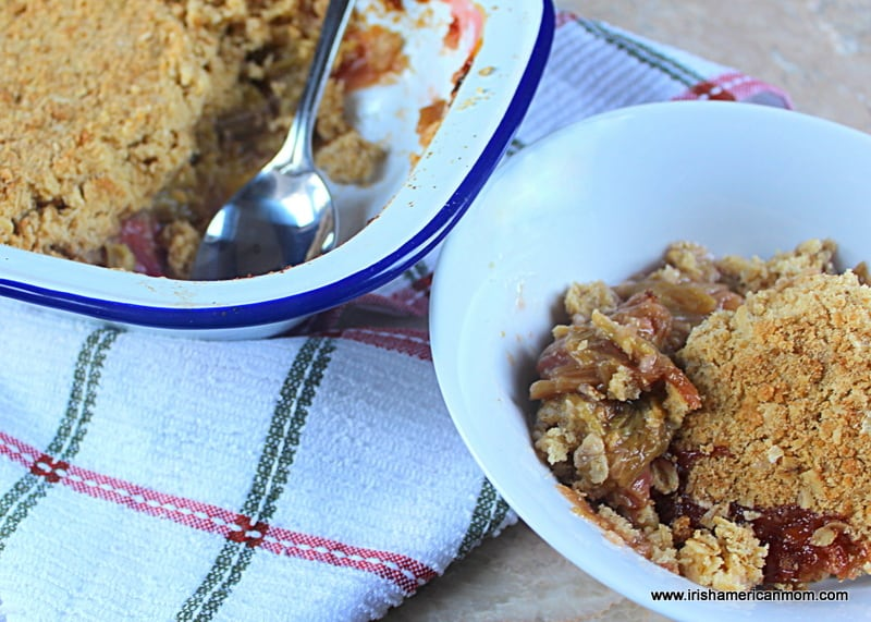 A serving of rhubarb crumble in a white bowl beside a casserole dish with a serving of crumble removed