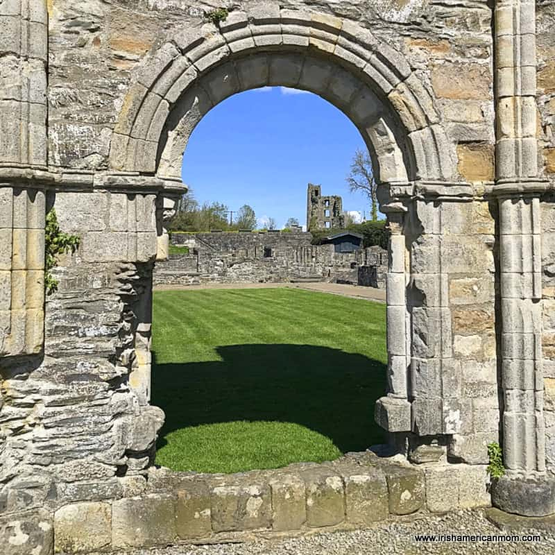 Looking through a stone archway at a ruined castle in Ireland