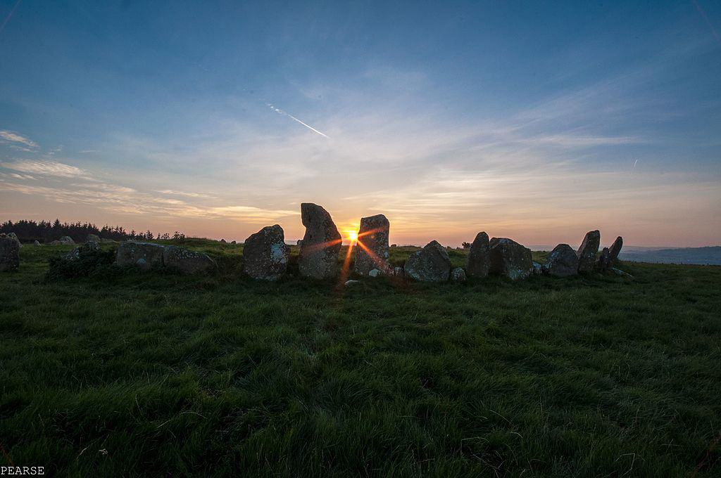 The sun shining through the stones of the Beltany Stone Circle in Ireland