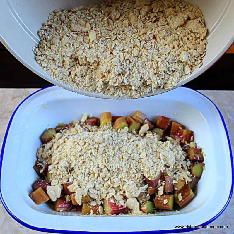 Pouring an oaty crumble mixture over rhubarb in a casserole