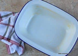 A buttered white enamelware casserole dish with a blue rim