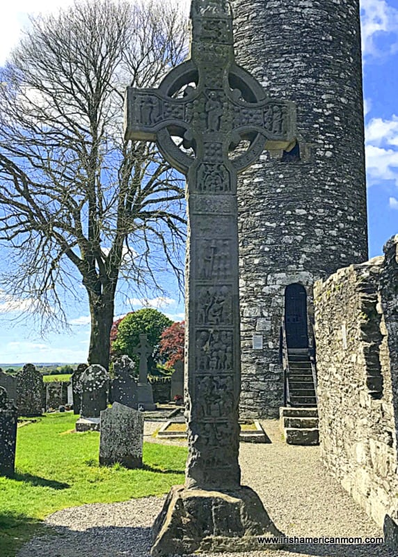 A Celtic Cross beside a stone round tower