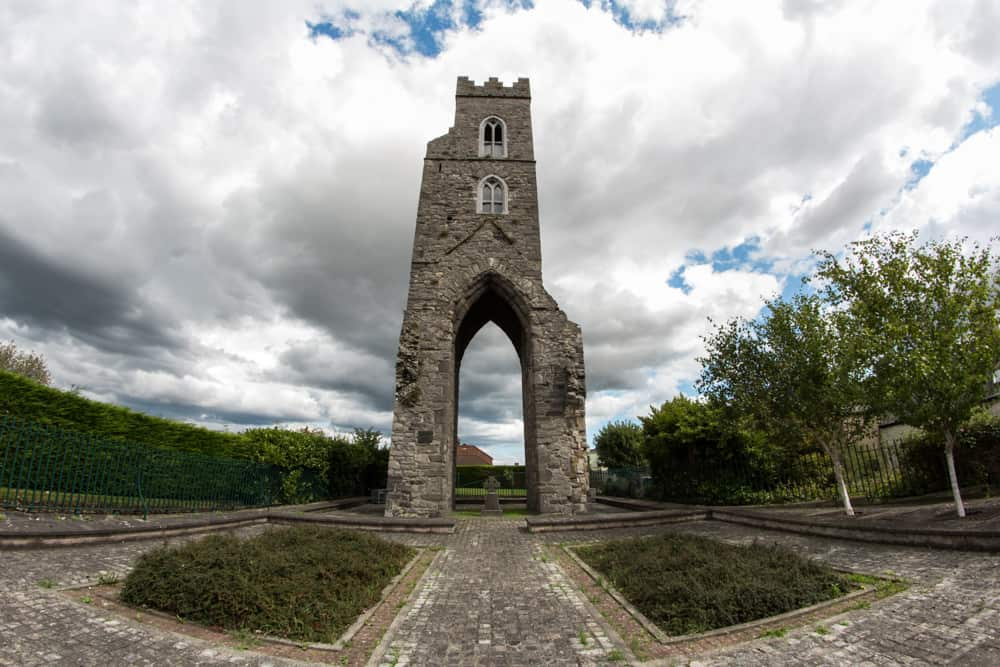 A belfry or church tower over the ruin of a tall arched church door