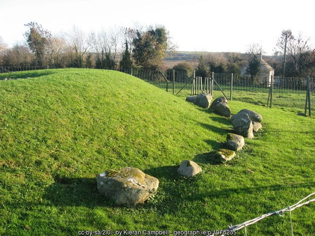A green mound surrounded by a small stone circle of standing stones