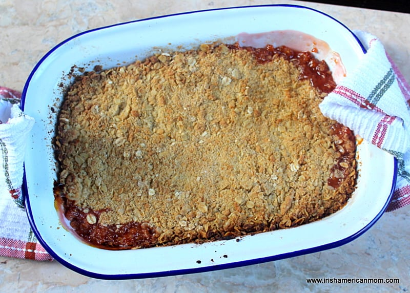 A rhubarb crumble fresh out of the oven with dishcloths to hold the hot surfaces.