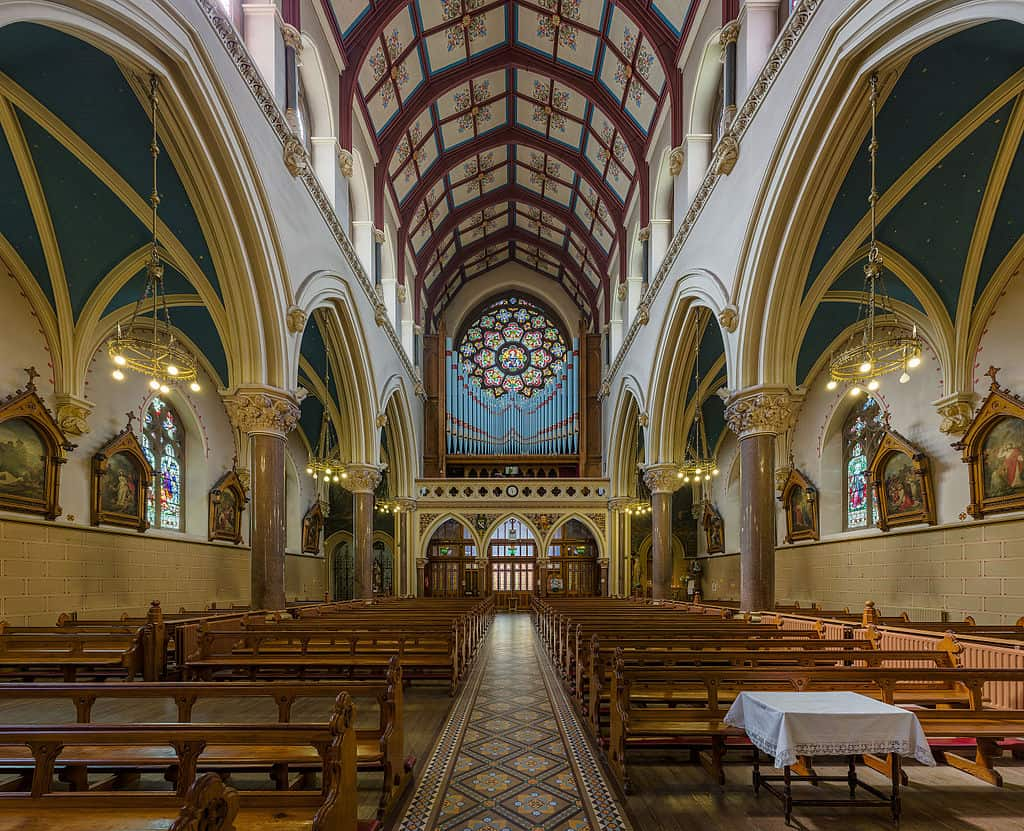 The nave of a church with a view of the pews and stations of the cross