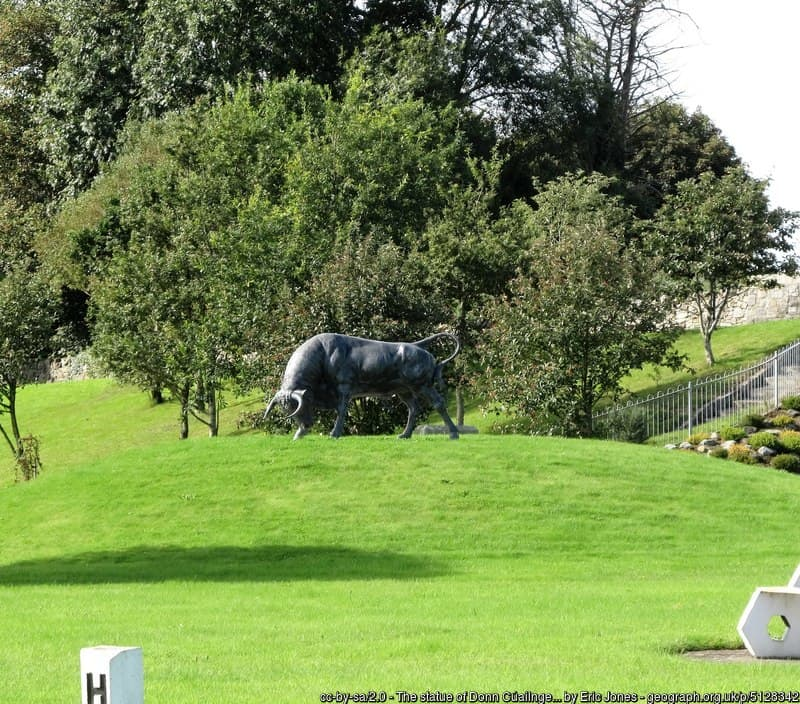 A sculpture of a bull on a green mound in a park