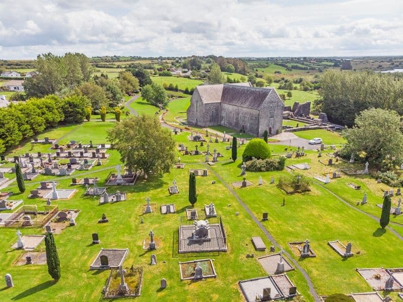 Aerial view of a church and graveyard in green fields