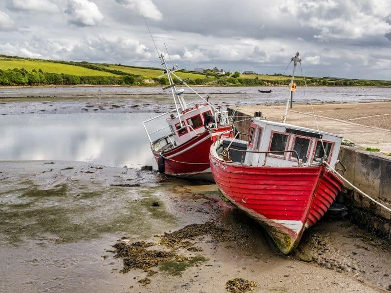 Red boats moored beside the quay or key when the tide is out in Ireland
