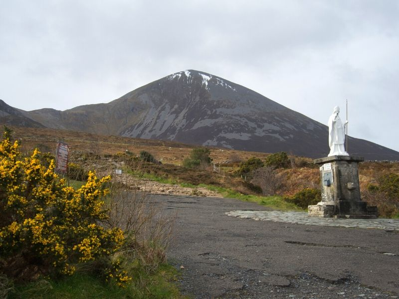 A white statue of Saint Patrick at the base of a steep mountain
