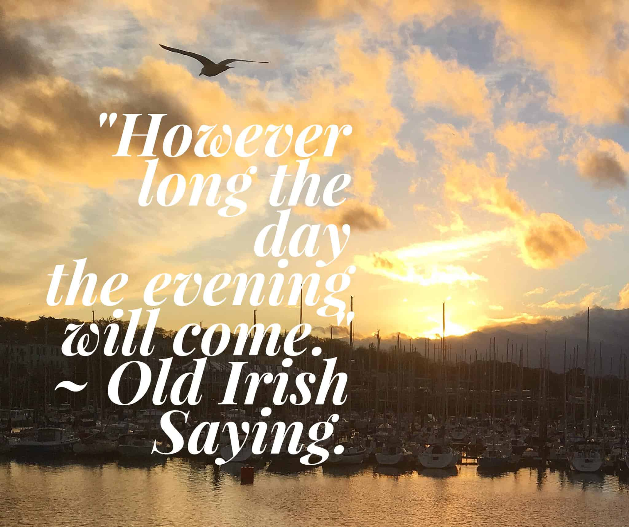 The setting sun over the boats at a marina illustrating the old Irish saying however long the day the evening will come