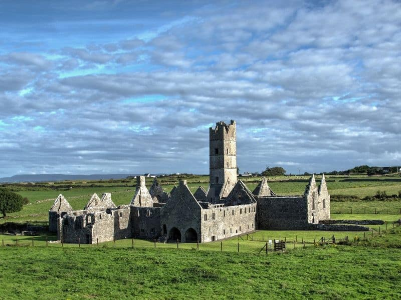 A ruined monastery with large square tower in a green field with a cloudy blue sky
