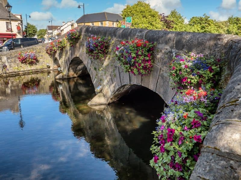 Arched bridge with flower baskets over a river