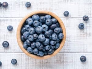 A wooden bowl with blueberries on a background of white plant with scattered blueberries all around