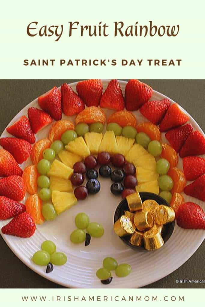 A fruit rainbow platter with shamrocks made of grapes and a bowl of rolos as a pot of gold