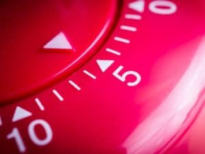 A close up view of a red cooking timer with the dial set just beyond 5 minutes