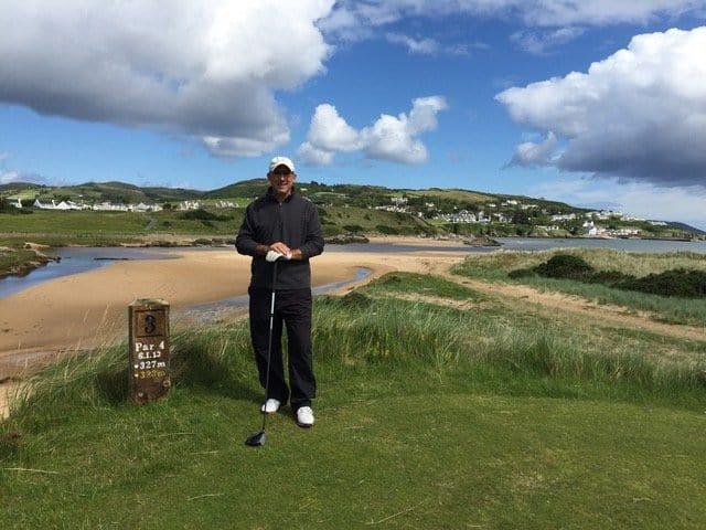Golfer at a tee beside a beach in Ireland