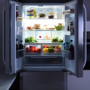 An open refrigerator with the light on showing food on the shelves