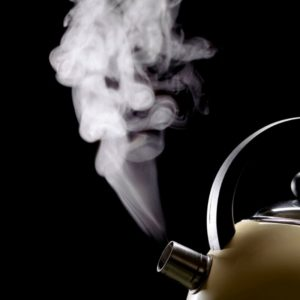White steam rising from the spout of a kettle against a black background