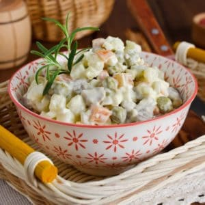 Russian salad of carrots, peas, and pickles covered in dressing in a bowl on a tray
