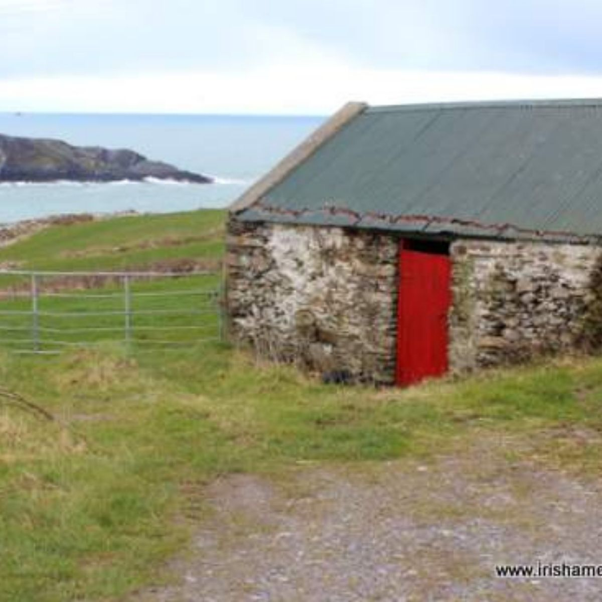 An iron gate beside an old shed with a red door on the coast