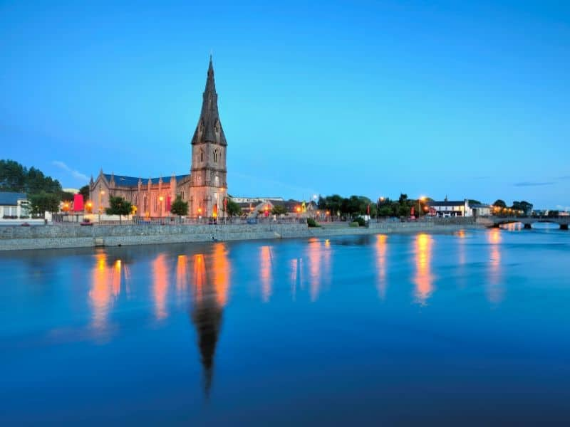 A grey cathedral with a high spire on a river bank with orange lights at twilight