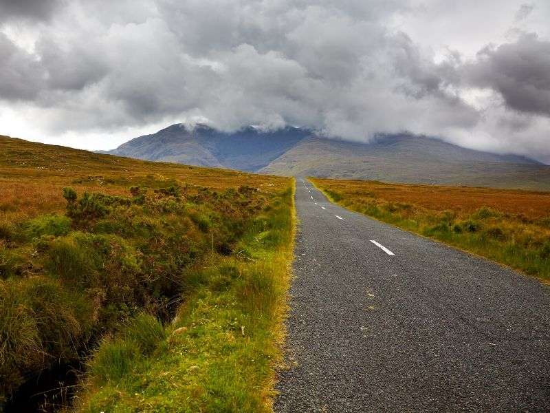 A mountain peak covered in gray clouds as a road approaches through bog land