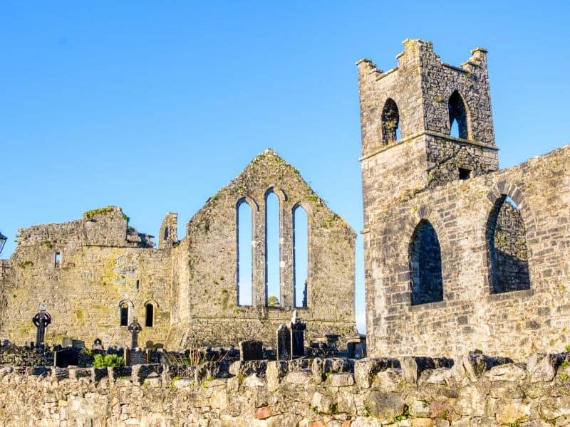 Ruined churches standing side by side and surrounded by a stone wall