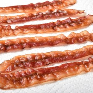 A row of cooked crispy bacon draining on white paper towels