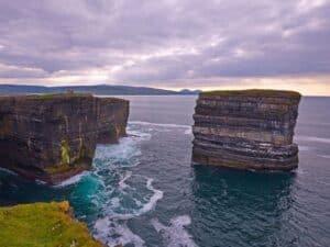 Sea stack in the ocean opposite craggy sheer cliffs