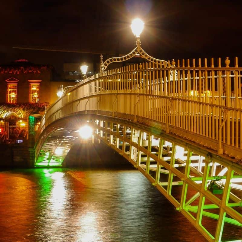 Green lights shining on an arched metal bridge over a river at night