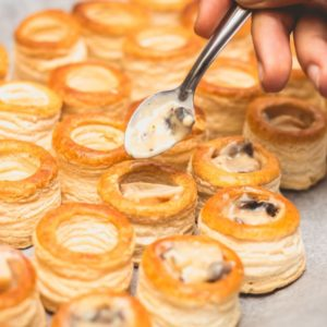 Rows of puff pastry shells being filled with spoonfuls of savory filling