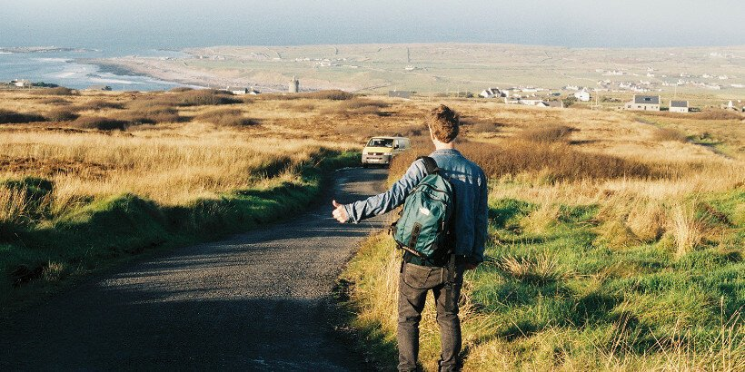 A man on the grassy verge of a road thumbing a lift from an approaching van
