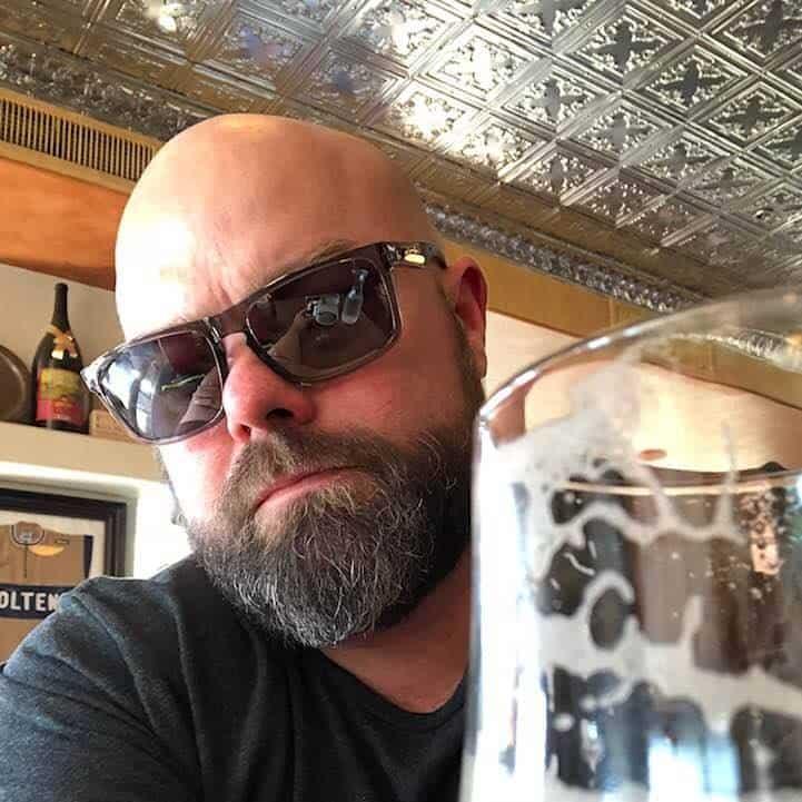 A bearded man with sun glasses in a pub with an empty beer glass