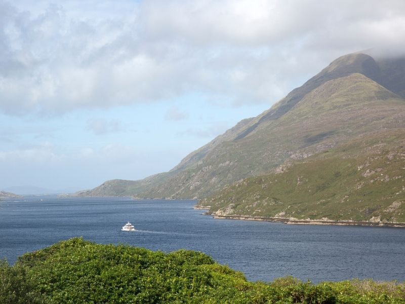 A boat travels on the waters of a fjord beside a tall mountain