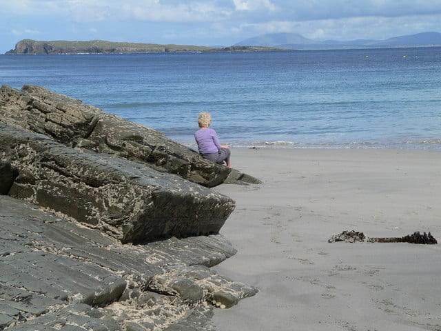 A blonde woman in a purple sweater sits on a rock by a sandy beach looking out to sea at a distant island