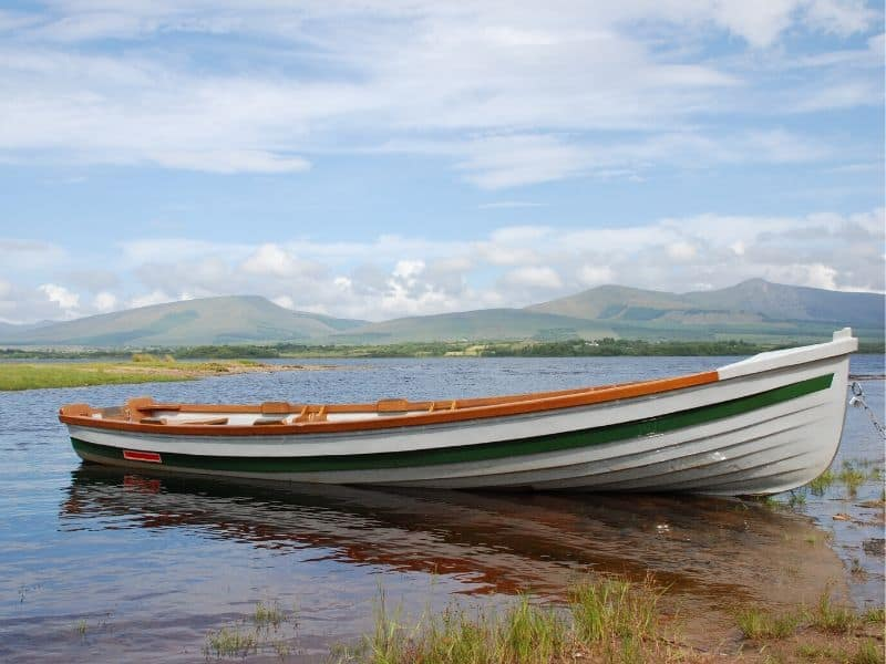A boat on a lake beside a beautiful mountain in Ireland
