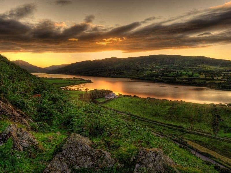 Orange skies reflecting on an Irish lake as the sun sets over a mountain