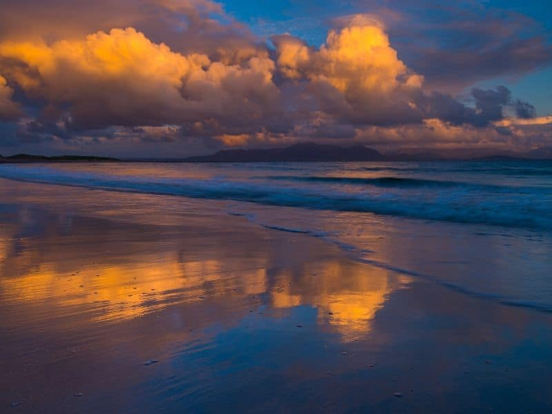 Clouds over a beach at sunset reflected on the wet sands