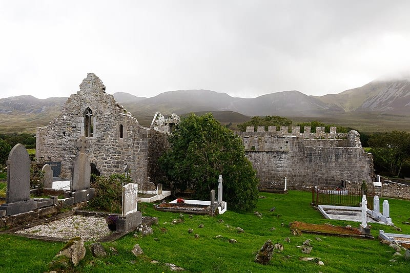 A ruined church beside foggy hills
