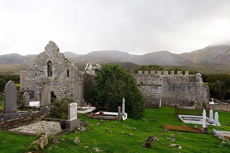 A ruined church beside foggy hills
