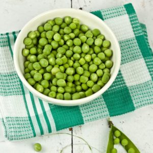 A white bowl of peas on a green and white checkered dish cloth