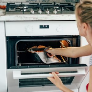A woman wearing an oven mitt to place a cake pan in a hot oven