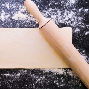 A sheet of puff pastry on a floured surface beside a rolling pin