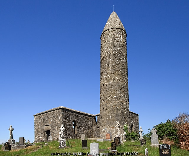 A stone tower or round tower by a ruined Irish church in a cemetery