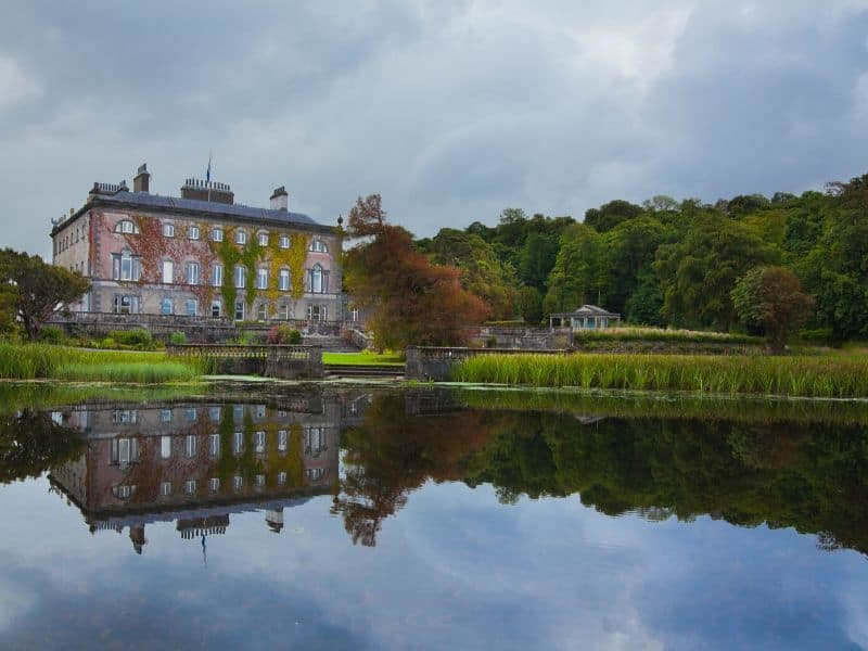 A large country house reflecting in a nearby lake