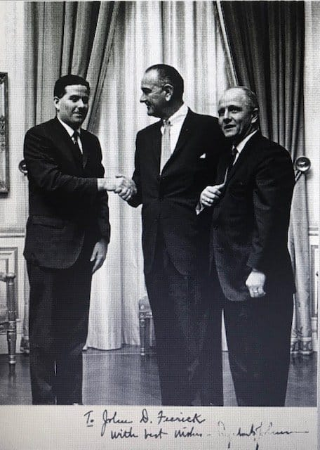Black and white photo of President Lyndon Johnson with two men