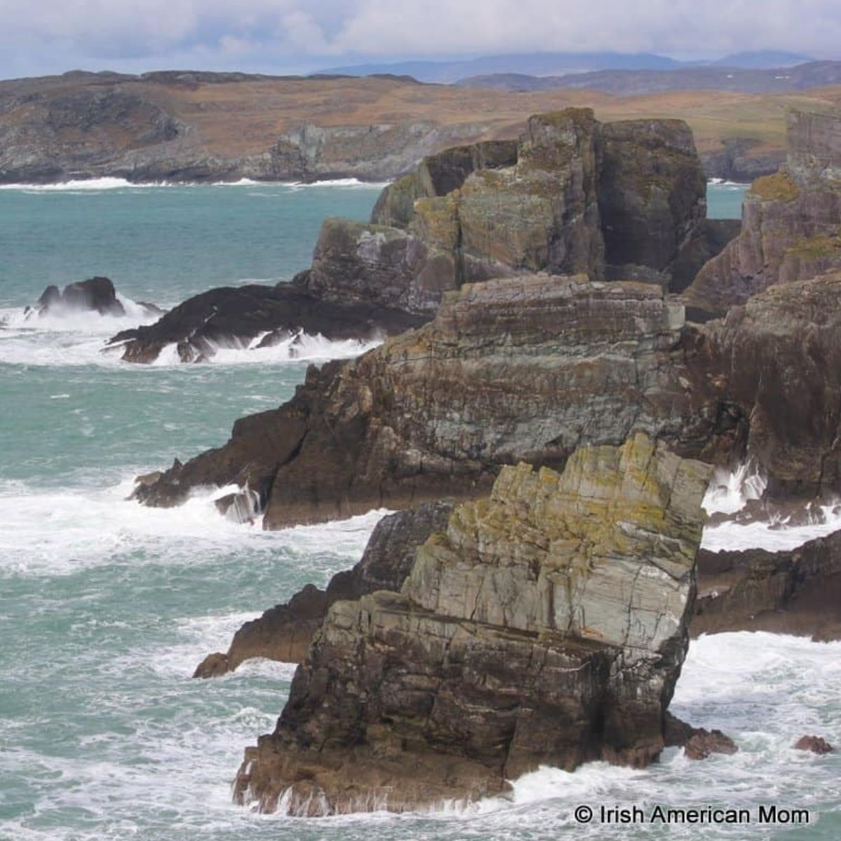 Three large rock formations jutting into the ocean in Ireland