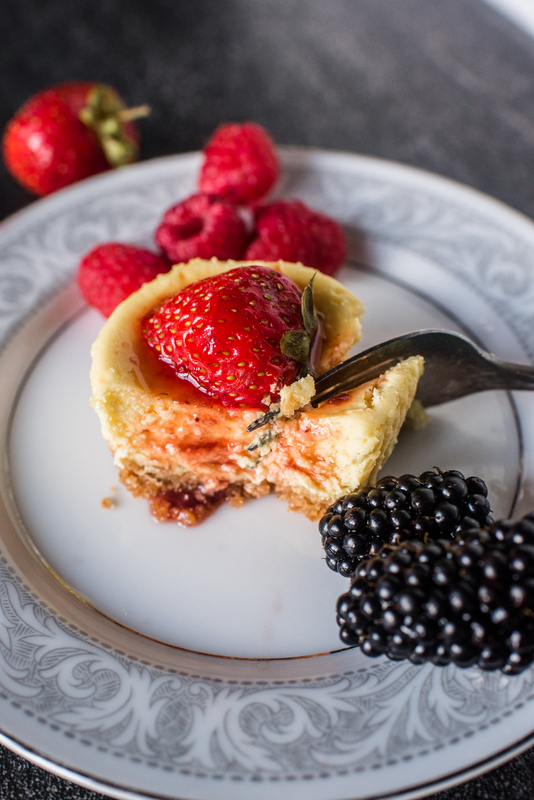 A fork cutting through a mini cheesecake with a strawberry on top and raspberries and blackberries beside it on a plate